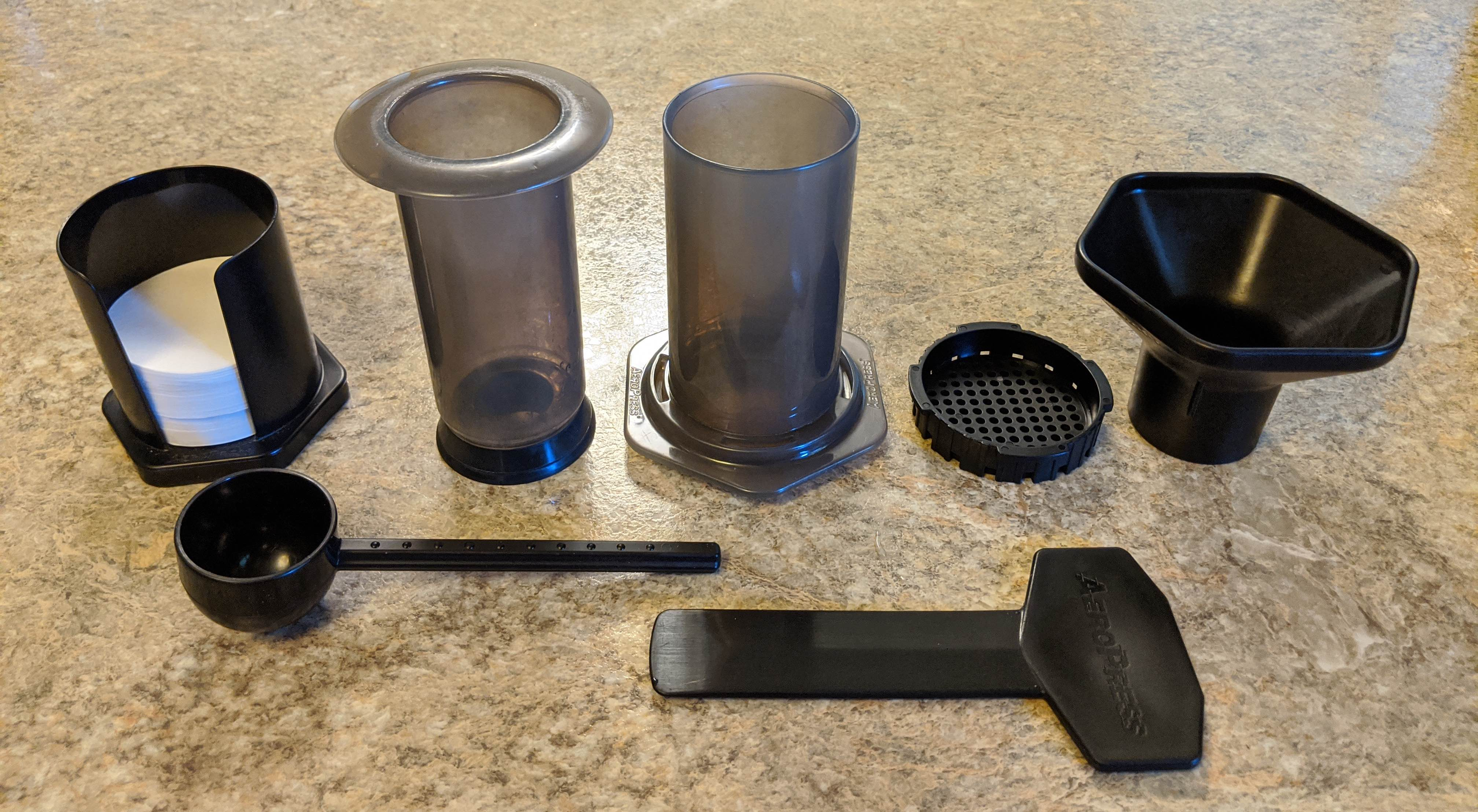 Aeropress components: filters, the press, filter holder, funnel, scoop, paddle.